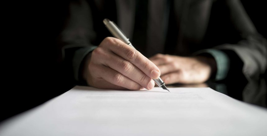 Closeup of lawyer or executive signing a contract, placed on black desk.