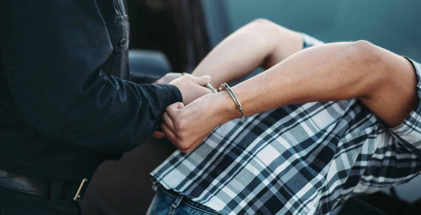 Police officer puts handcuffs on a car thief, policeman arrests the driver violator on road. Cop at the work. Law protection concept, professional safety control